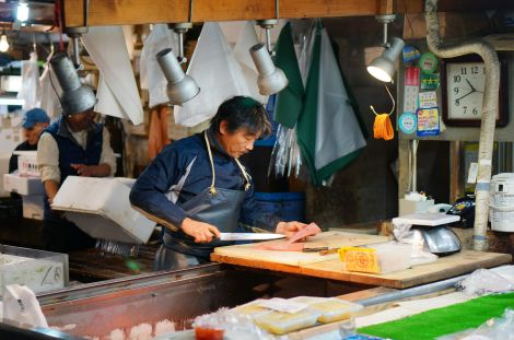 In the closing hours, this fishmonger remains hard at work slicing fish